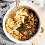 overhead view of white bowl with homemade spaetzle and mushroom gravy