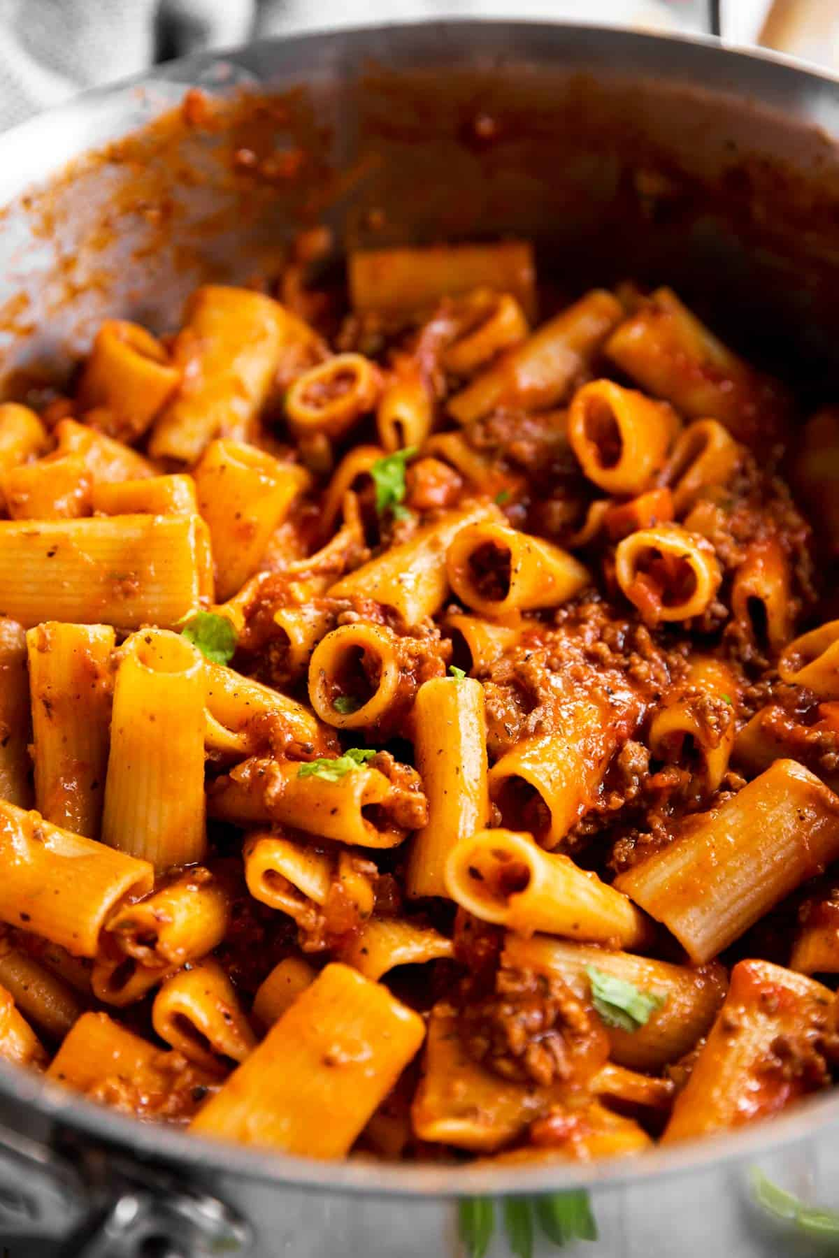 close up of rigatoni bolognese in pan
