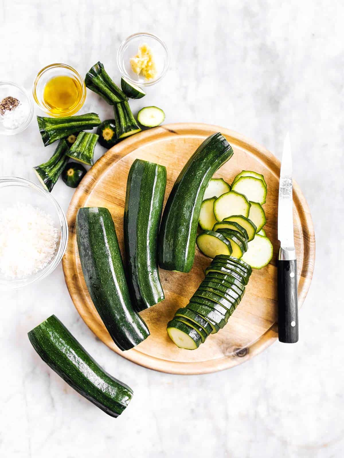 wooden board with partly sliced zucchini and a knife