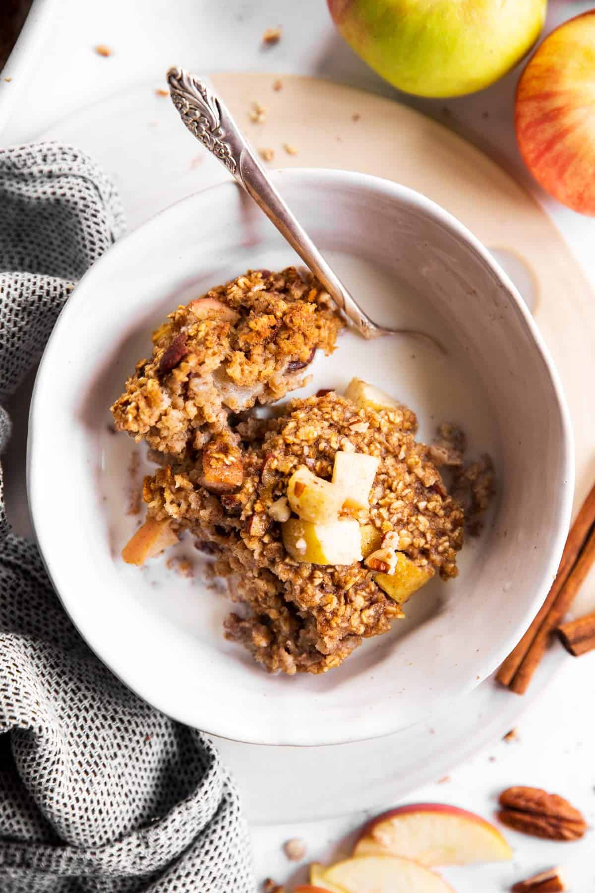 overhead view of white bowl with apple baked oatmeal and milk