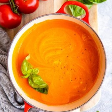 red cast iron pot with homemade tomato soup, surrounded by fresh tomatoes and basil