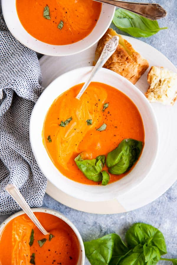 three bowls filled with homemade garlic roasted tomato soup