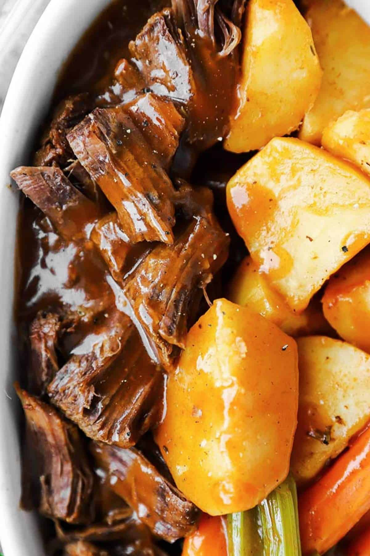 close up photo of beef roast with gravy in dish with vegetables