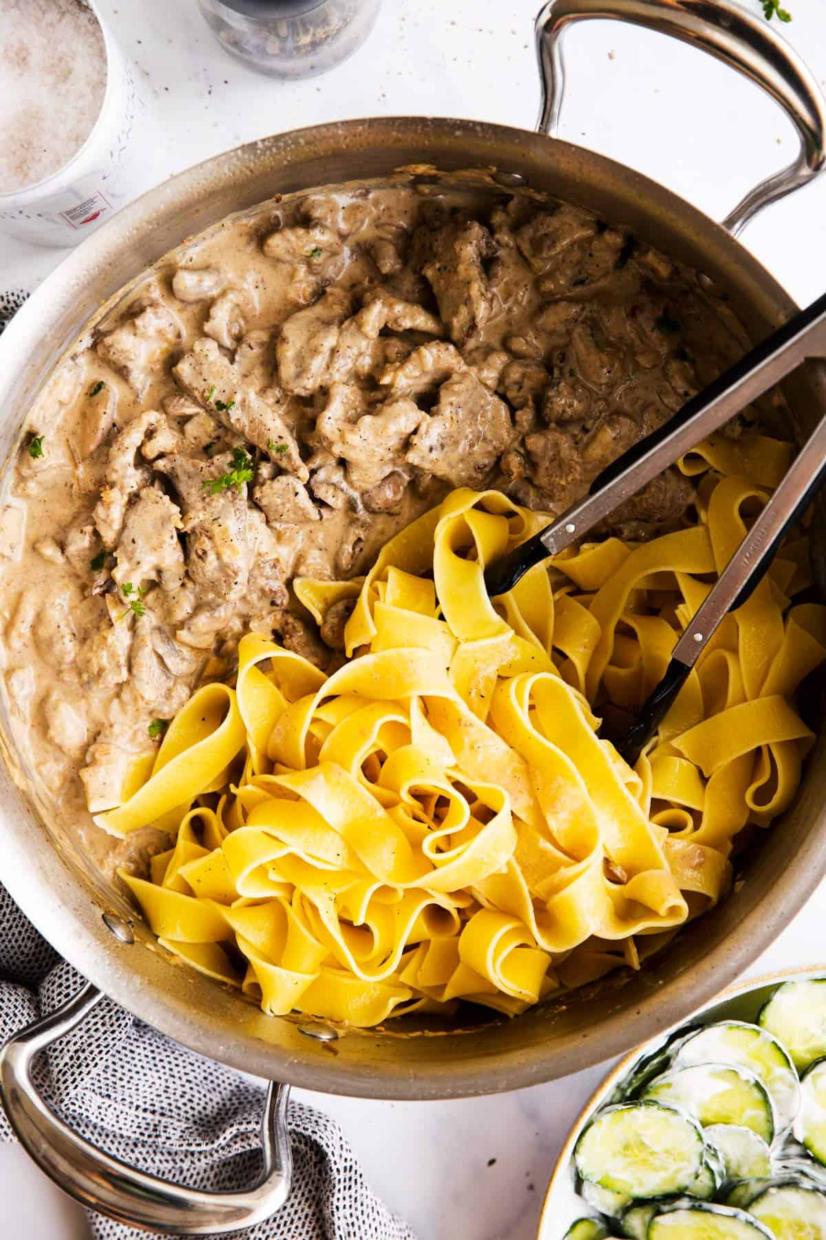 top down view on a skillet with beef stroganoff and buttered noodles