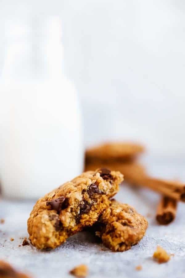 broken up close up photo of a Pumpkin Chocolate Chip Oatmeal Cookies in front of a milk bottle