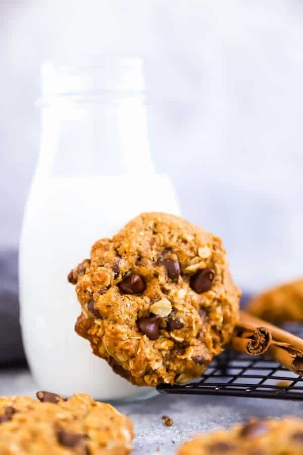 broken up close up photo of a Pumpkin Chocolate Chip Oatmeal Cookies leaning against a milk bottle