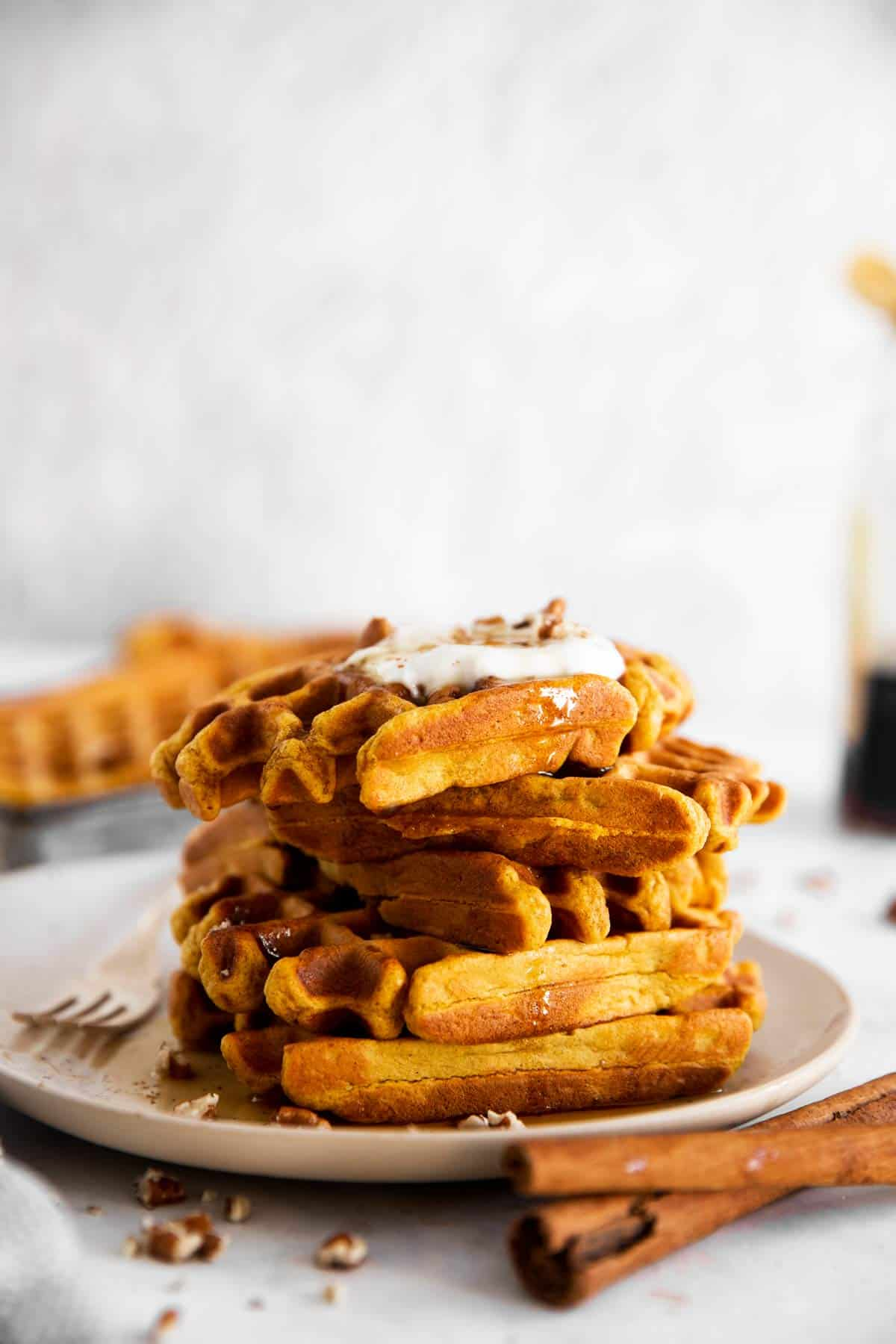 stack of pumpkin waffles on a white plate