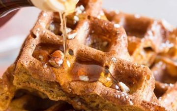close up photo of maple syrup being poured over pumpkin spice waffles