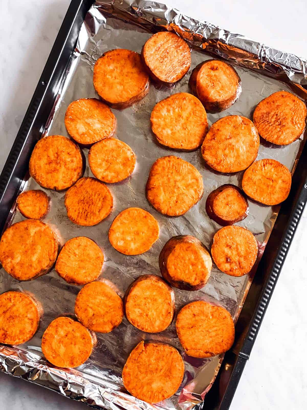 baking tray with raw sweet potato slices