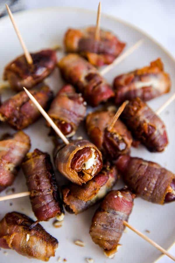 close up photo os a plate with goat cheese stuffed and bacon wrapped dates