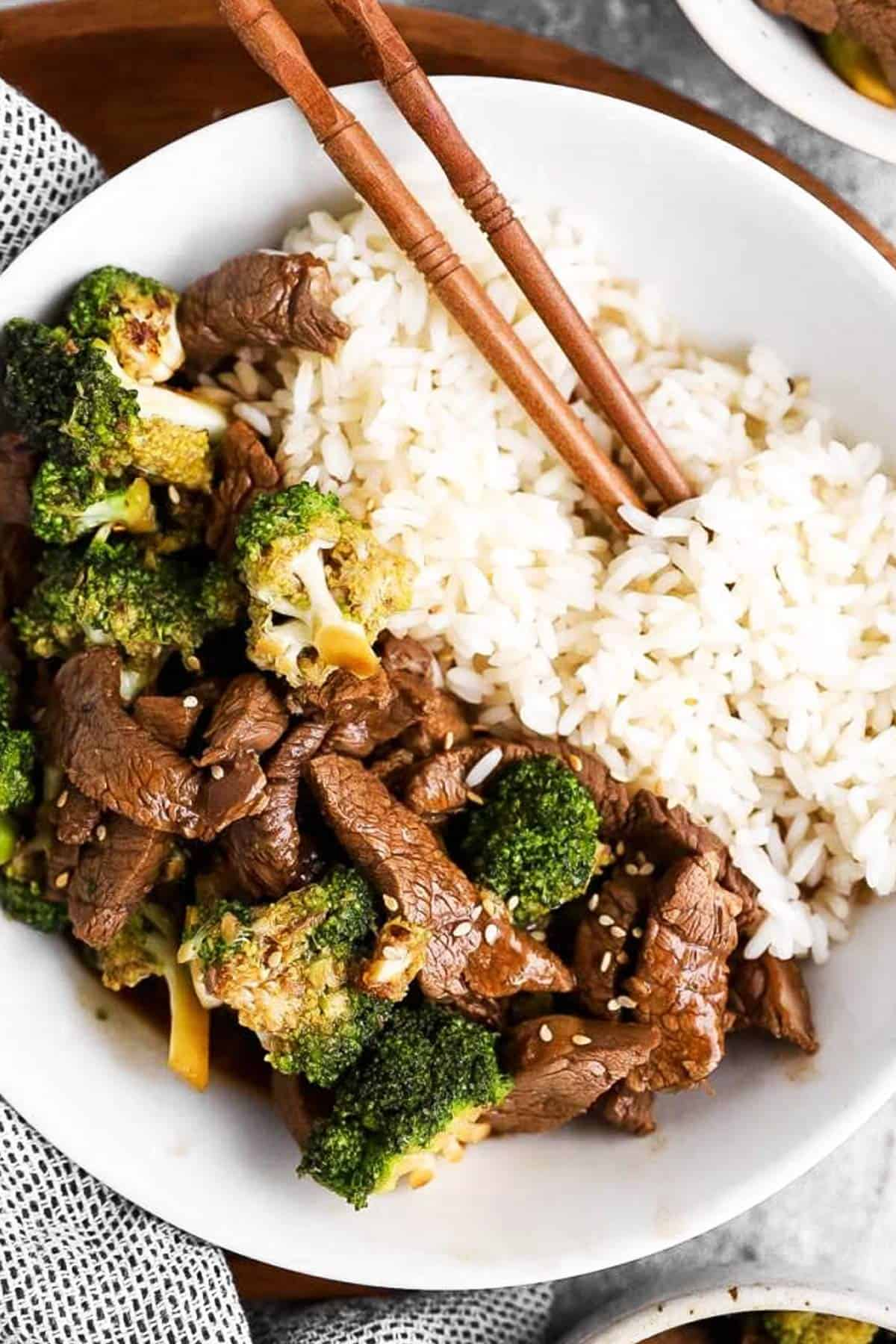 close up photo of beef, broccoli and rice in a white bowl