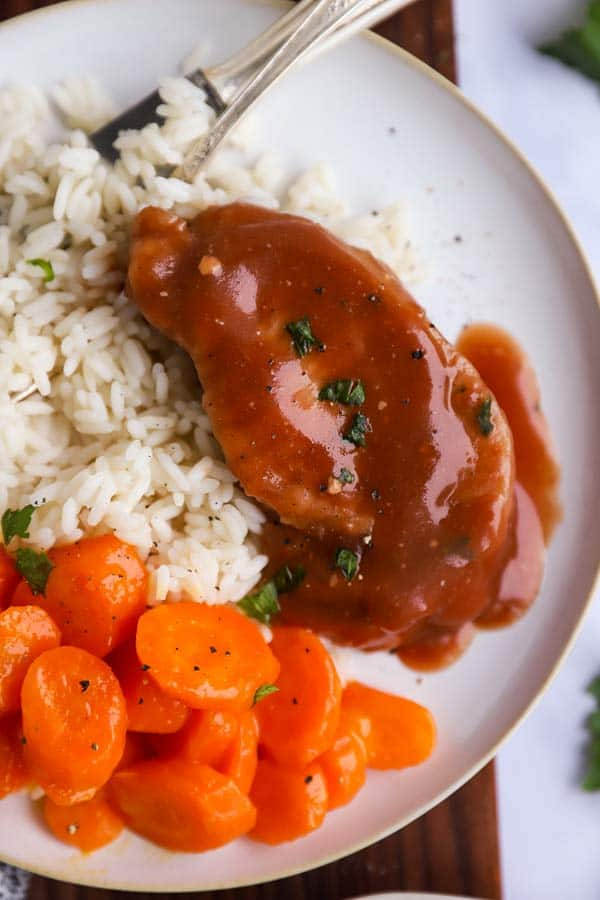 close up of a plate with rice, carrots and glazed pork chops