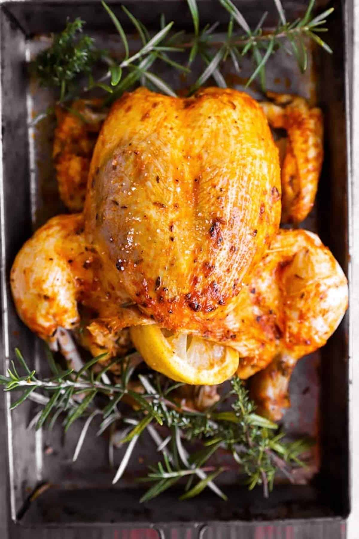 Whole slow cooker chicken on a sheet pan with fresh rosemary