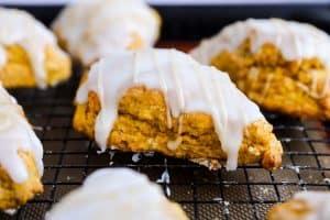 close up photo of a glazed pumpkin scone