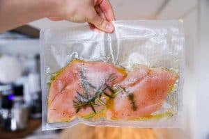 holding a sous vide bag with uncooked chicken