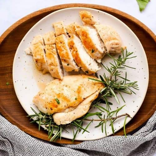 sliced chicken breast on a white plate, sitting on a wooden platter