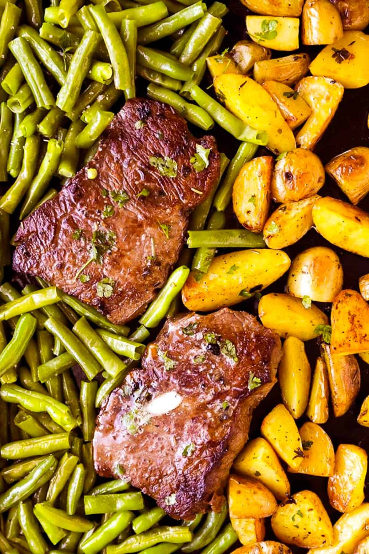 overhead view of potatoes, green beans and steak on sheet pan
