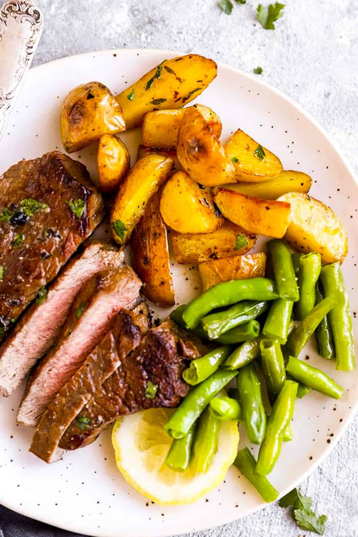plate with sliced steak, potatoes and green beans