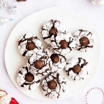 white plate with chocolate crinkle blossom cookies on a marble surface surrounded by festive elements
