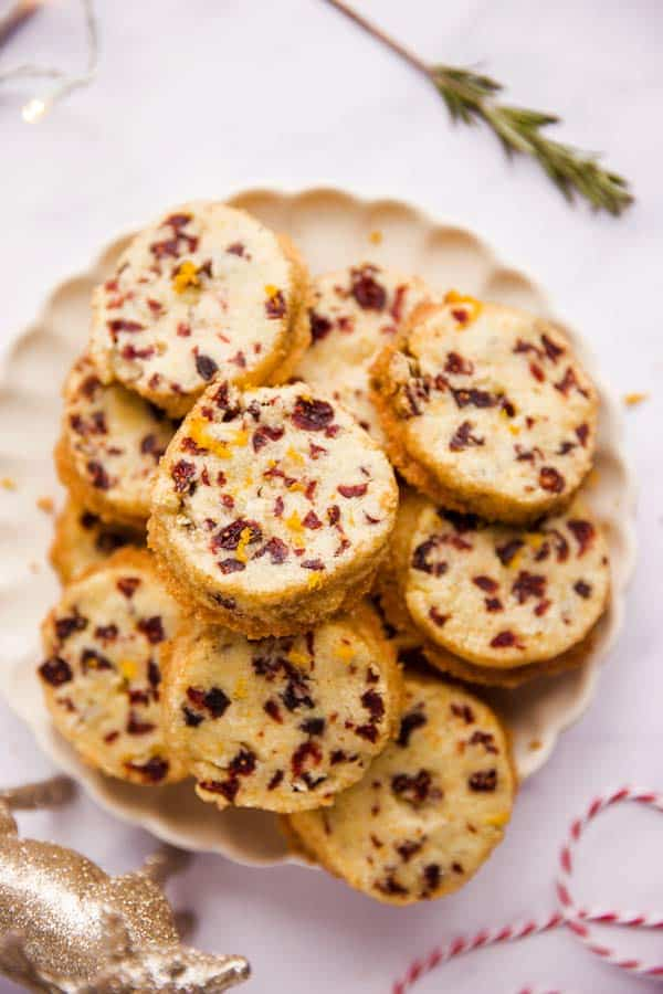 plate filled with cranberry orange shortbread cookies on a marble surface