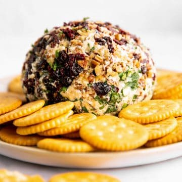 cheeseball sitting on platter with crackers