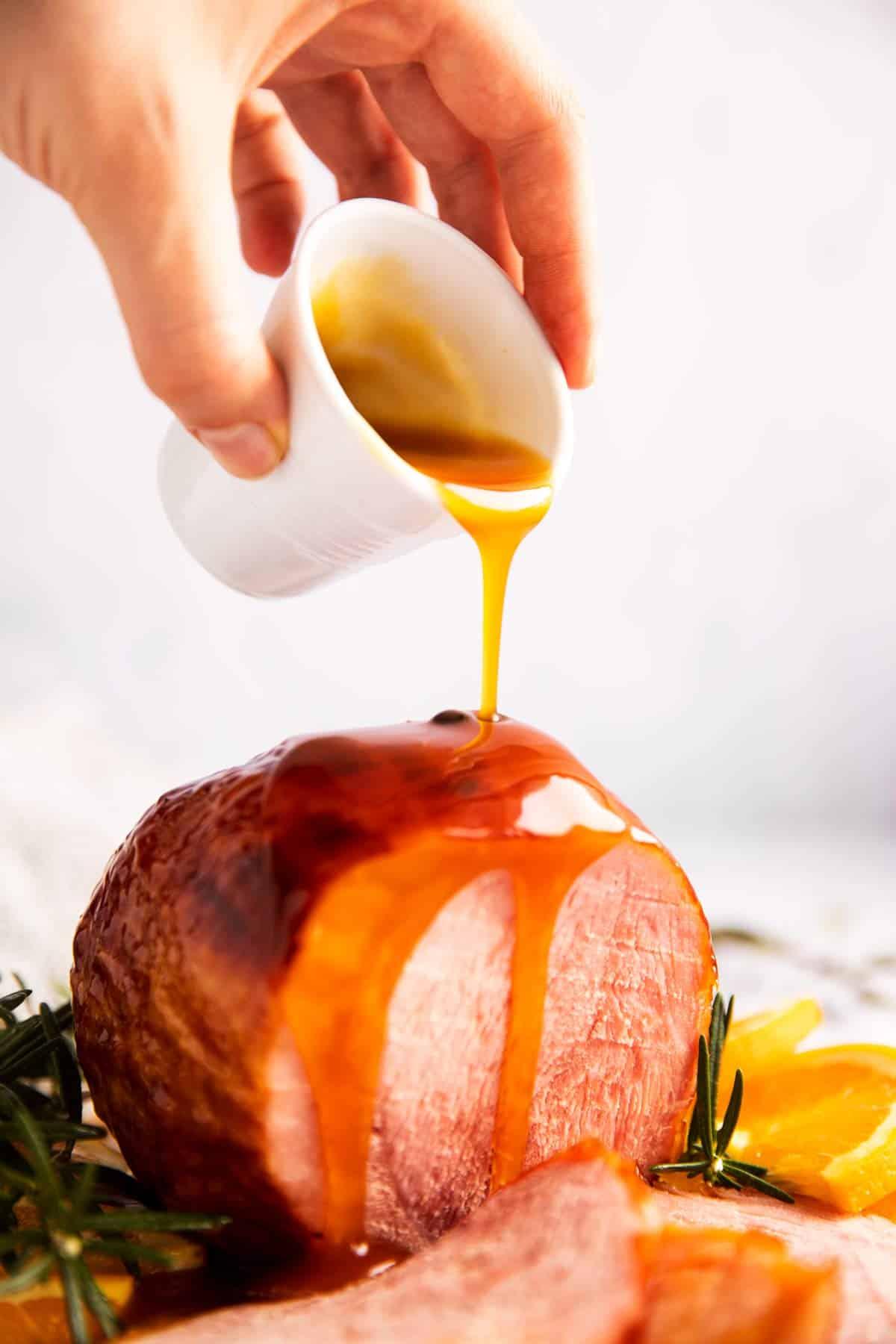 female hand drizzling honey glaze over ham