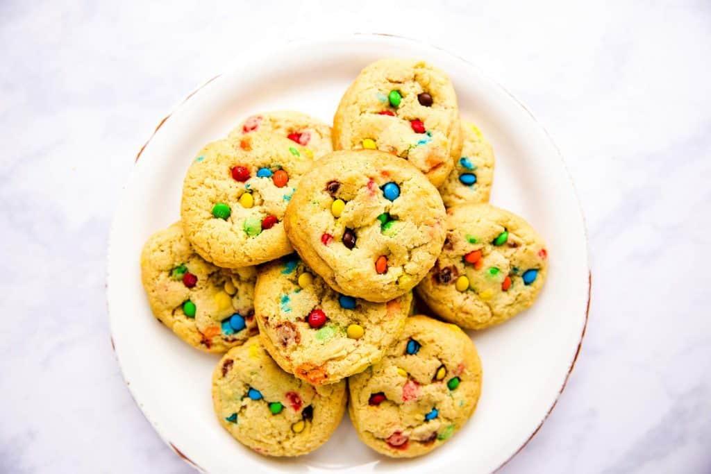 plate with m&m cookies on a white marble surface
