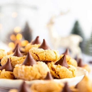 piles of peanut butter blossom cookies on a plate in front of festive decor