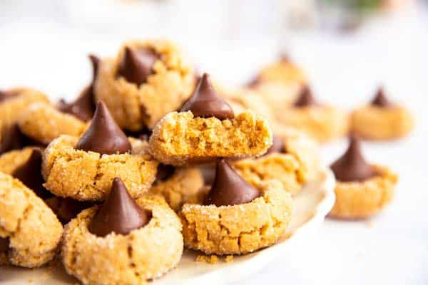 image of a cookie plate with the focus on a halved peanut butter blossom
