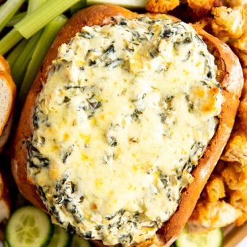 vertical image of wooden board with bread bowl filled with spinach artichoke dip, surrounded by vegetables and bread