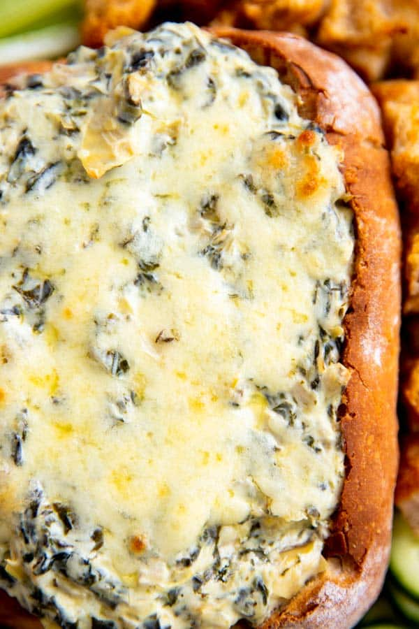 close up photo of a bread bowl filled with spinach artichoke dip