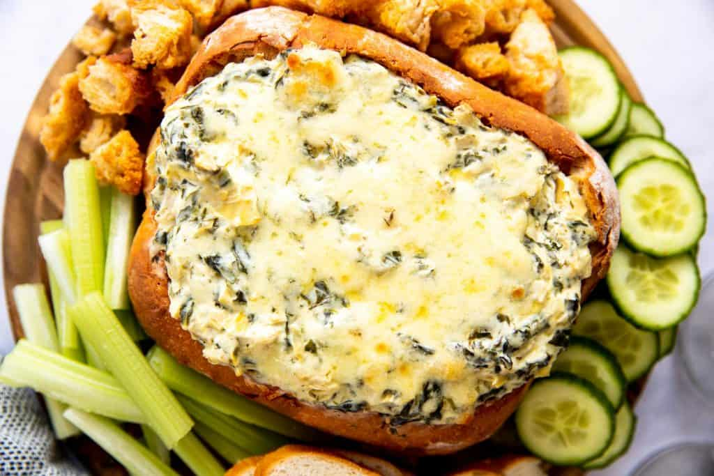 wooden board with bread bowl filled with spinach artichoke dip, surrounded by vegetables and bread