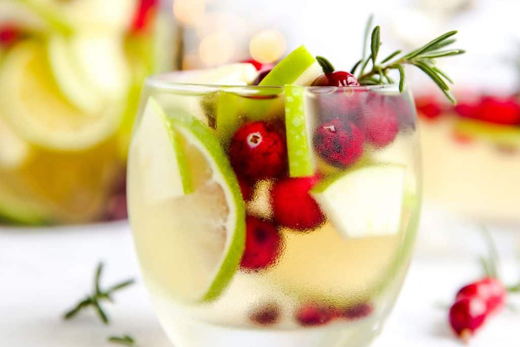 tumbler with lime, cranberry, apple, rosemary and white wine sangria