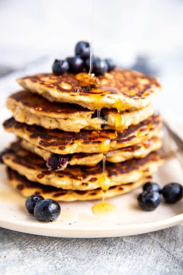 picture of a stack of pancakes with syrup drizzling over