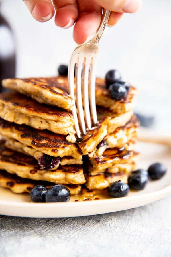 sticking a fork into a stack of blueberry oatmeal pancakes