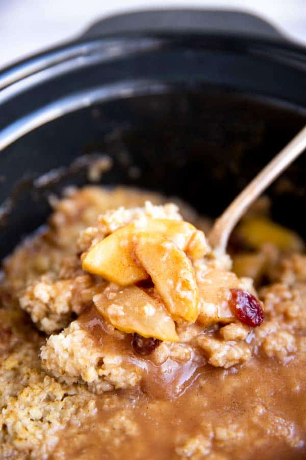 close up photo of cooked apples on top of oatmeal in slow cooker