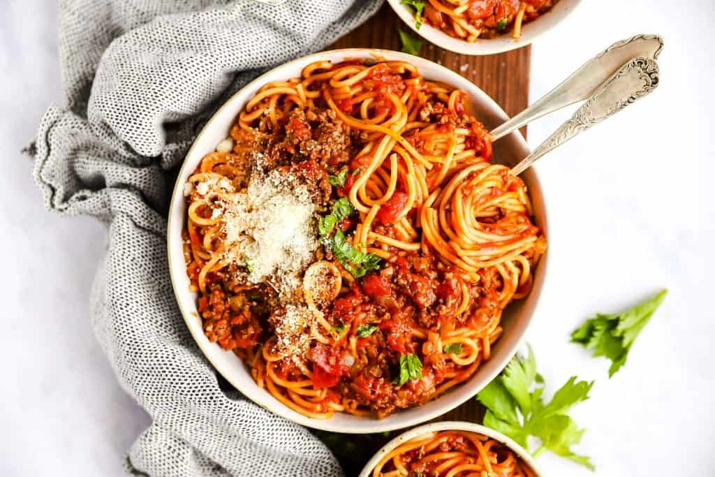 bowl filled with spaghetti and meat sauce on top of a wooden board on a light surface