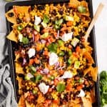 overhead view of nachos on dark colored sheet pan