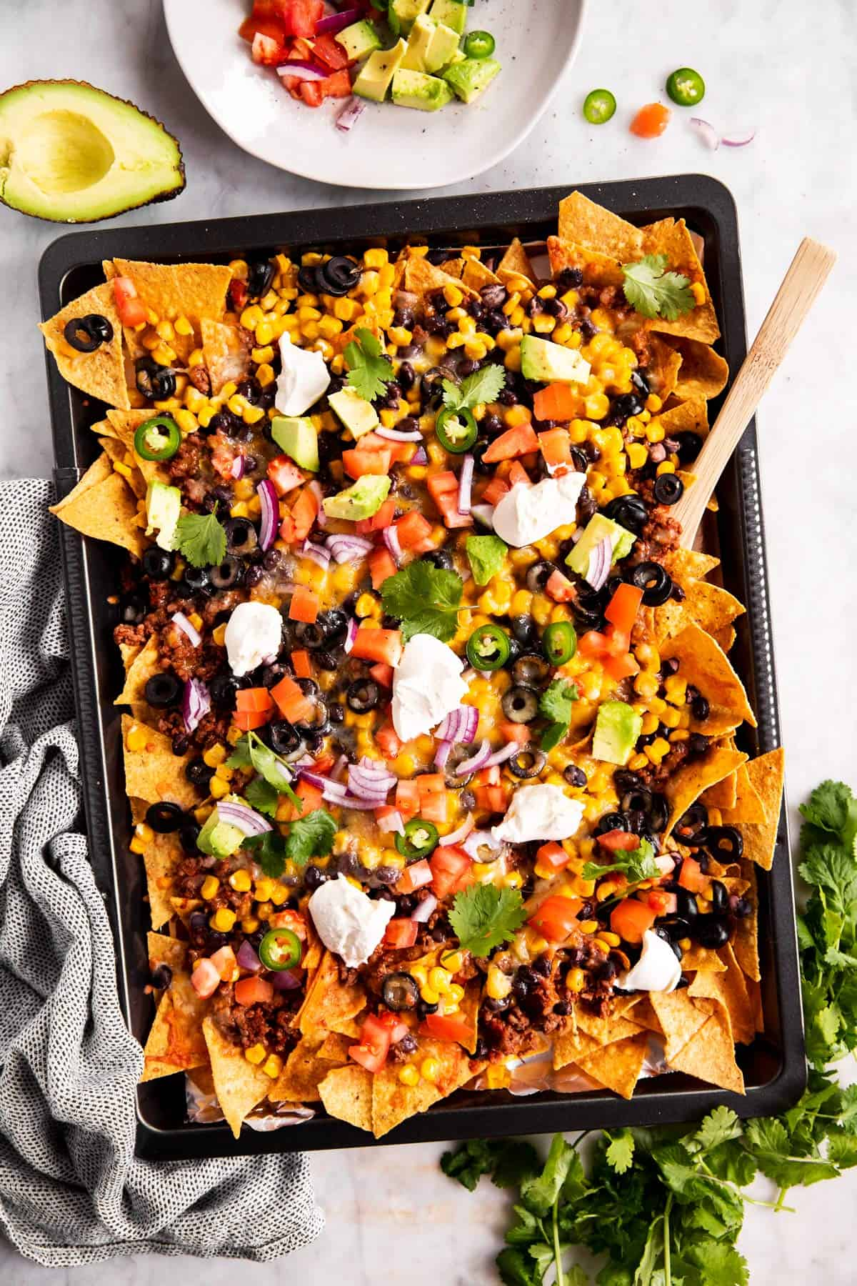 overhead view of nachos on dark colored sheet pan