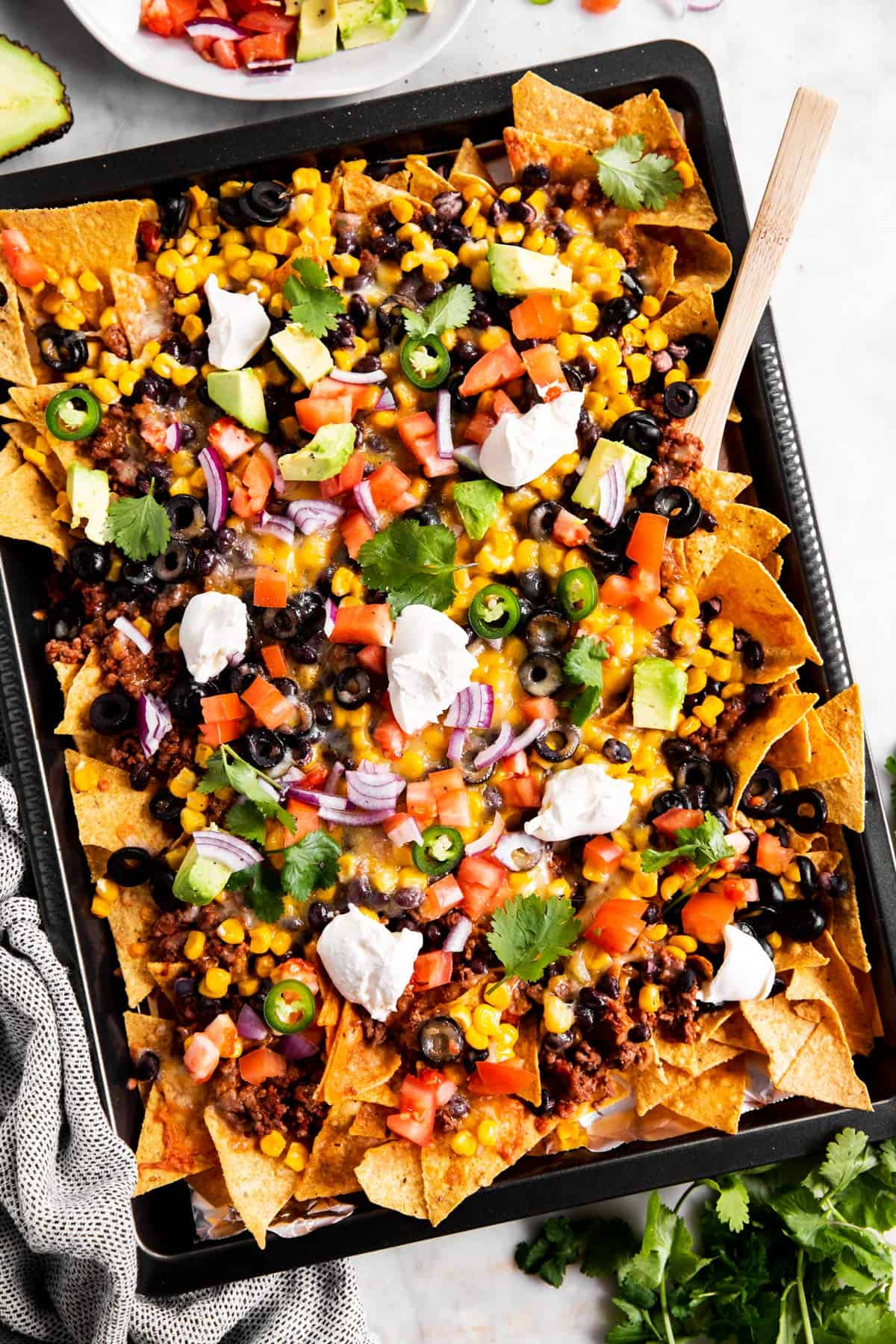 sheet pan with nachos and toppings from above