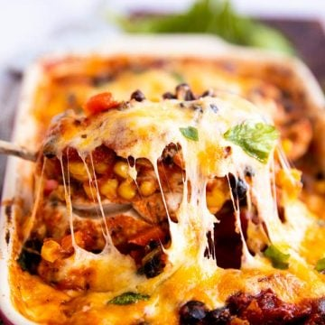 lifting a cheese covered chicken breast out of a casserole dish