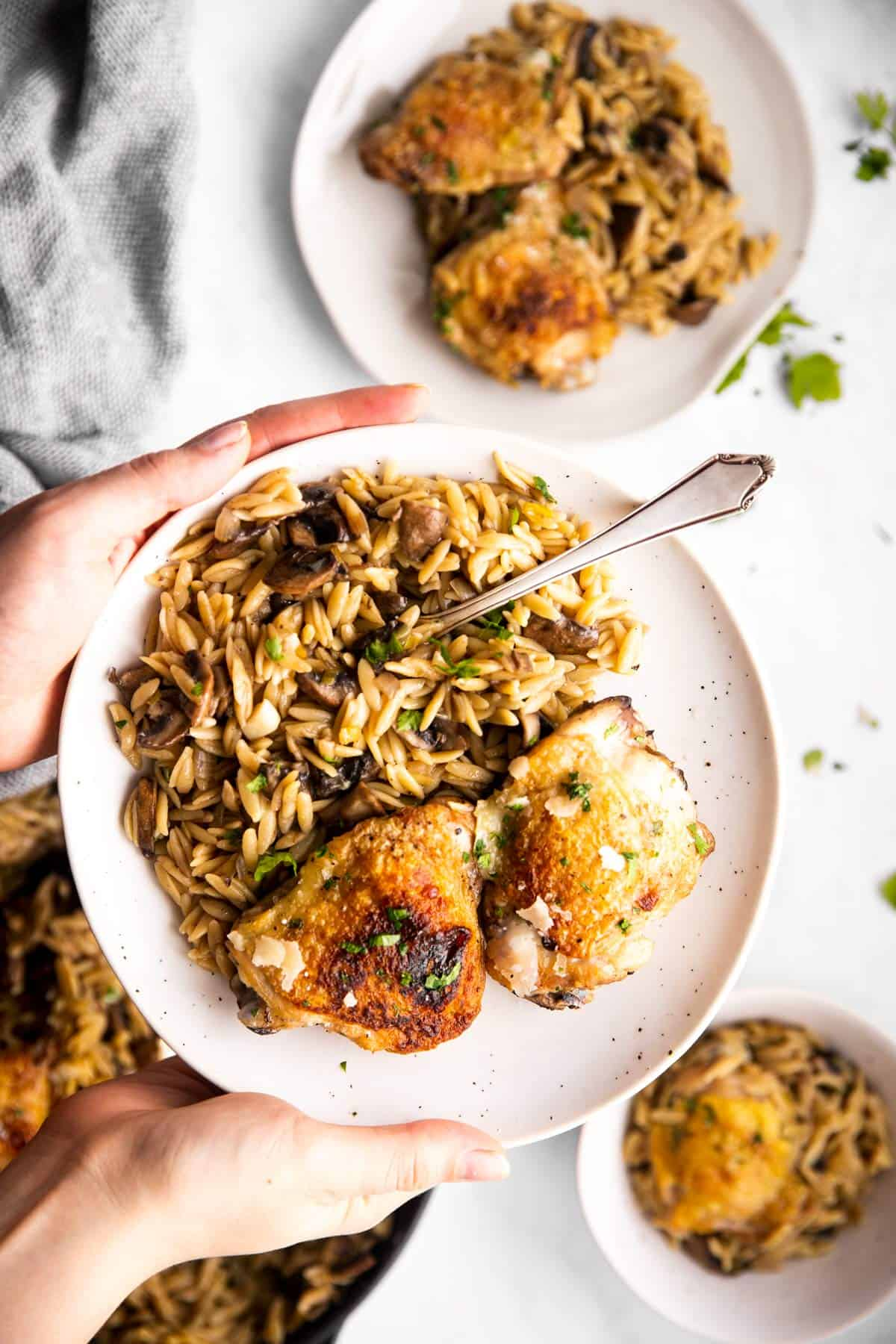 female hands holding white plate with mushroom orzo and chicken thighs
