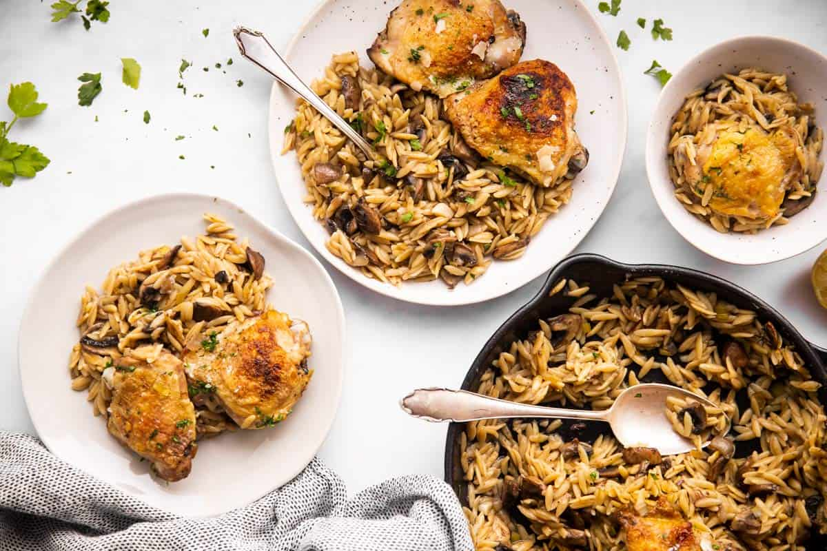mushroom orzo and chicken skillet on white tabletop with several plates around