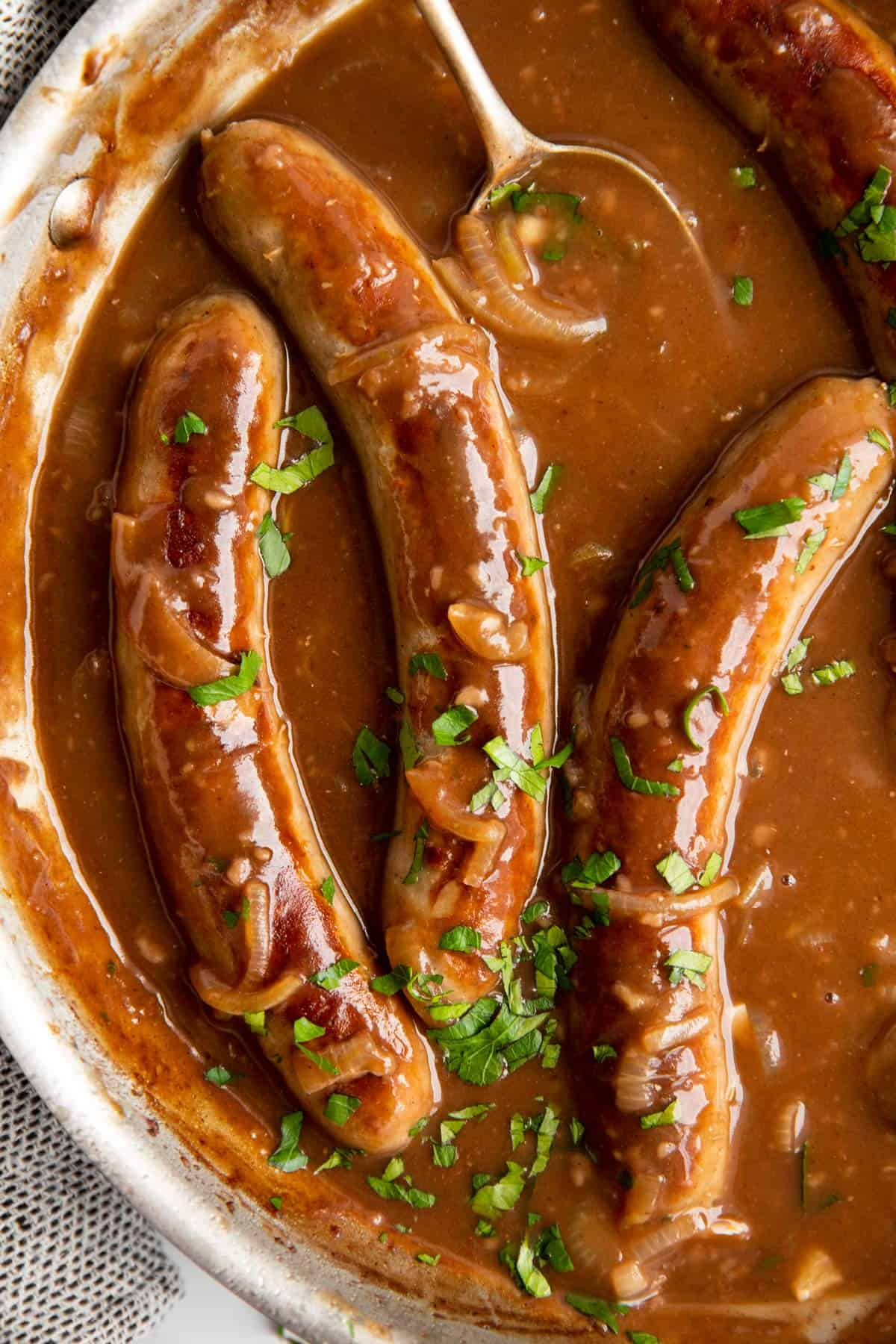 close up photo of sausage in a pan with onion gravy