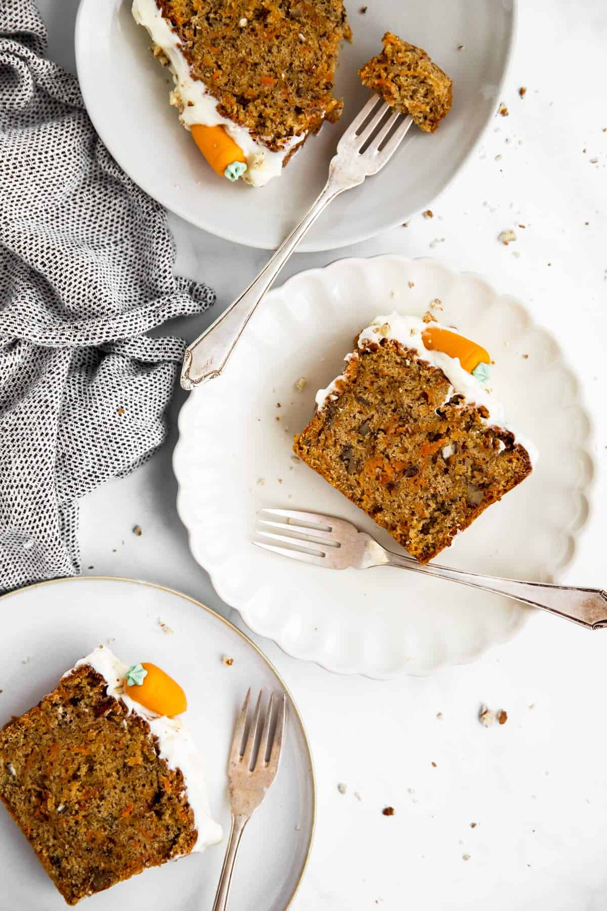 three plates with slices of carrot cake loaf