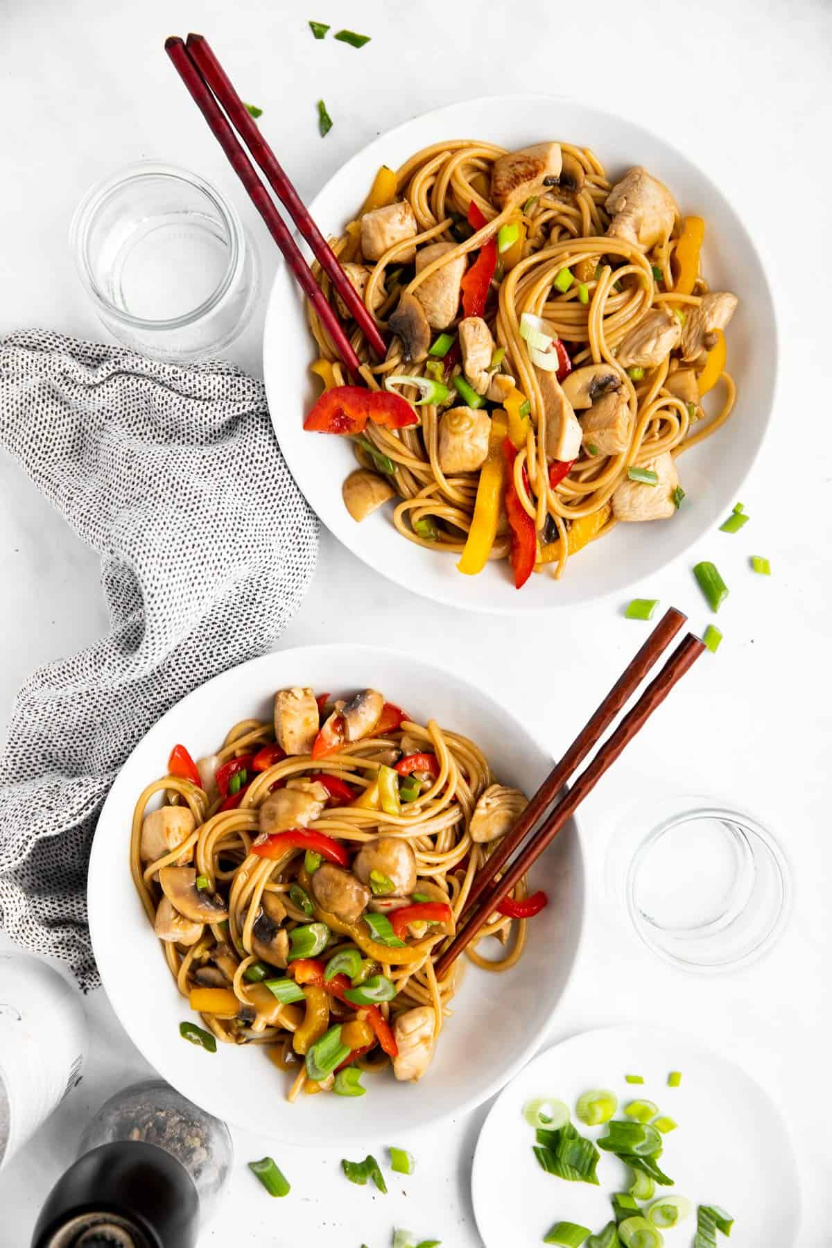 two white plates with chicken lo mein and chopsticks on a bright table