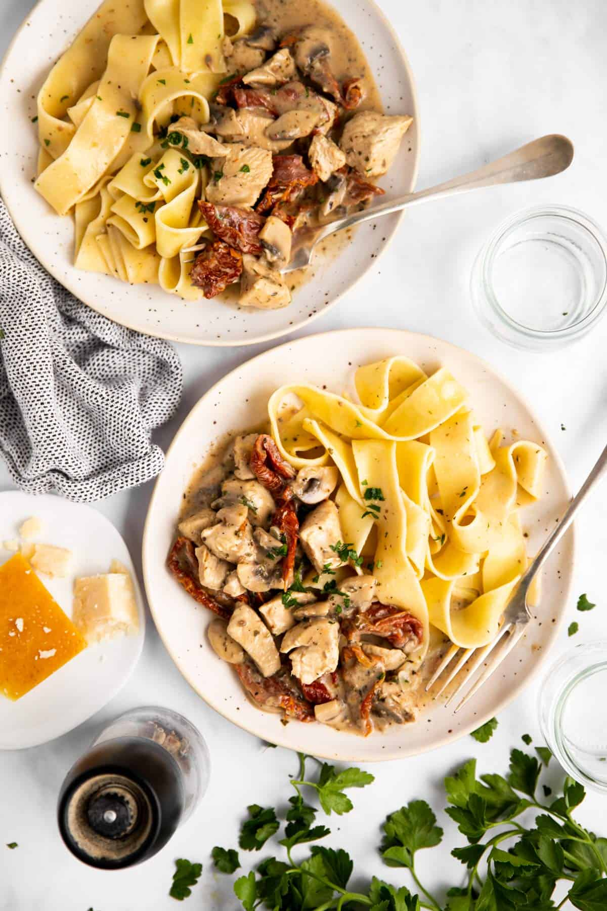 top down view on two plates with chicken pasta