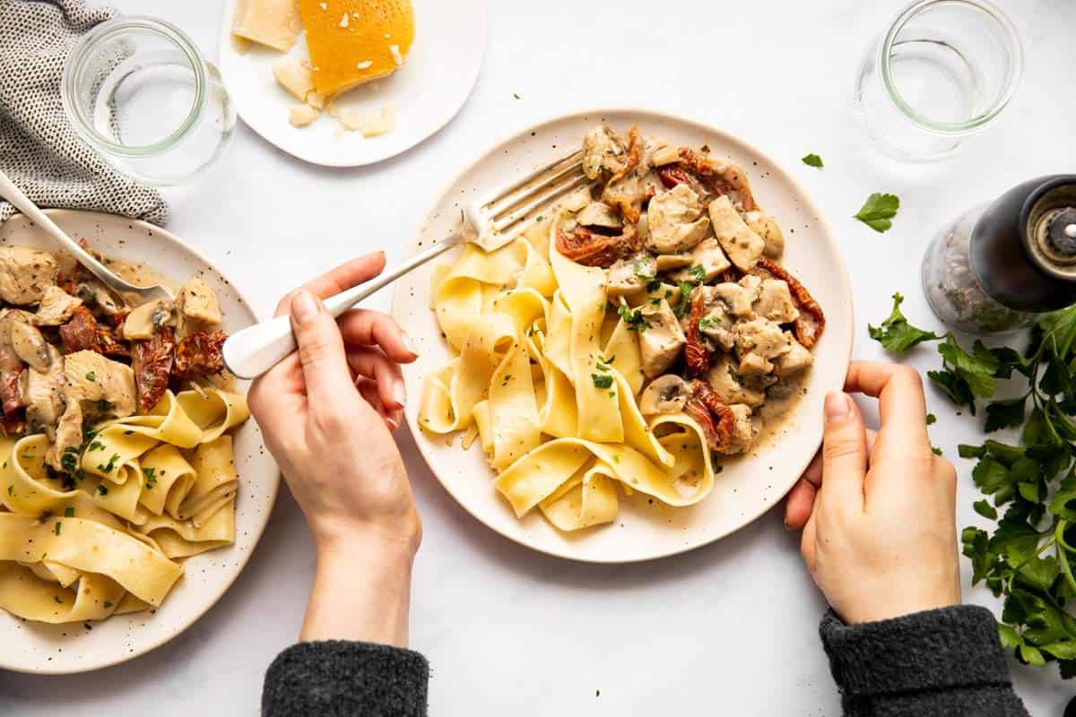 top down view on female hands holding a plate of chicken and pasta