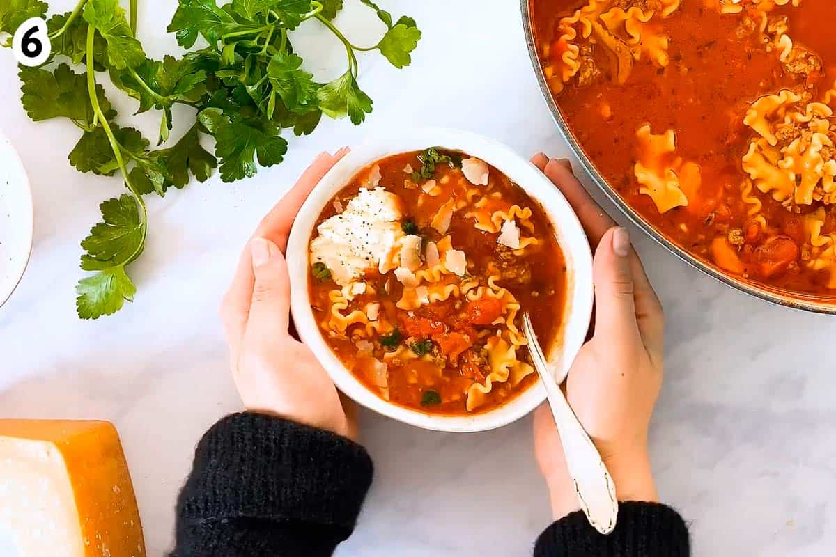 female hands holding bowl with Lasagna Soup