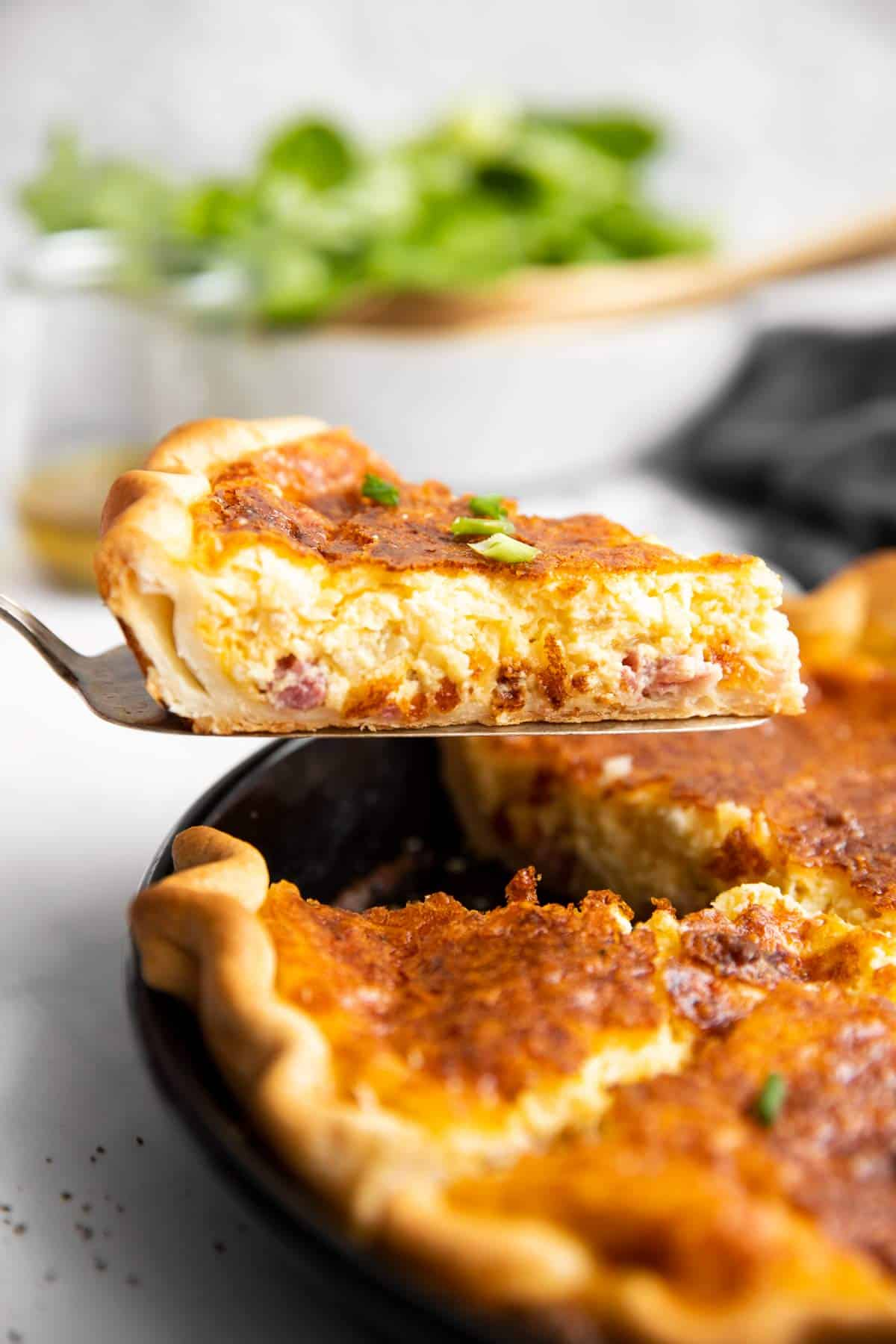 lifting a slice of Quiche Lorraine out of the pie dish